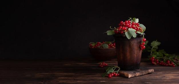 Letnie jagody, dojrzałe jagody czerwonej porzeczki w glinianej misce na ciemnym tle, baner, z bliska.