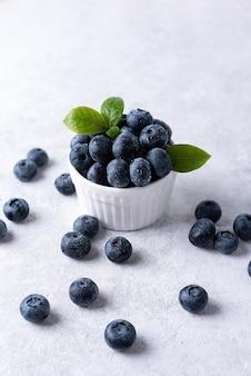 Letnie jagody, dojrzałe jagody w misce na białym tle, zdrowa żywność.
