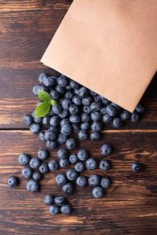 Letnie jagody, dojrzałe jagody wysypujące się z papierowej torby na zakupy na ciemnym tle drewnianych, widok z góry.