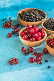 Letnie jagody mieszają się na niebieskim betonowym tle borówki czerwone czarne porzeczki i wiśnie