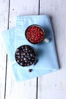 Letnie jagody w kolorowych kubkach na kolorowej drewnianej powierzchni