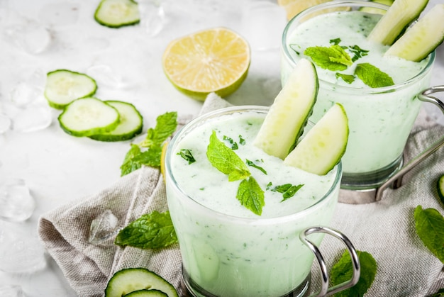 Letnie jedzenie orzeźwiające dania zimna zupa ogórkowa z awokado z ziołami i miętą z kieliszkami z plasterkami ogórka na białym betonowym stole ze składnikami