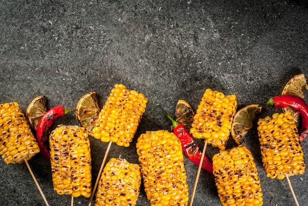 Letnie jedzenie. pomysły na grilla i imprezy przy grillu. grillowana kukurydza grillowana na ogniu. z odrobiną sera (meksykańskie eloty), ostrą papryczką chili i cytryną. na ciemnym kamiennym stole. widok z góry