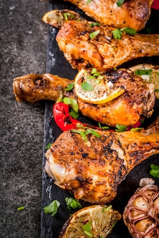 Letnie jedzenie. pomysły na grilla, przyjęcie z grilla. udka z kurczaka, skrzydełka z grilla, smażone w ogniu. z ostrą papryczką chili, cytryną i sosem bbq. ciemny kamienny stół, miejsce