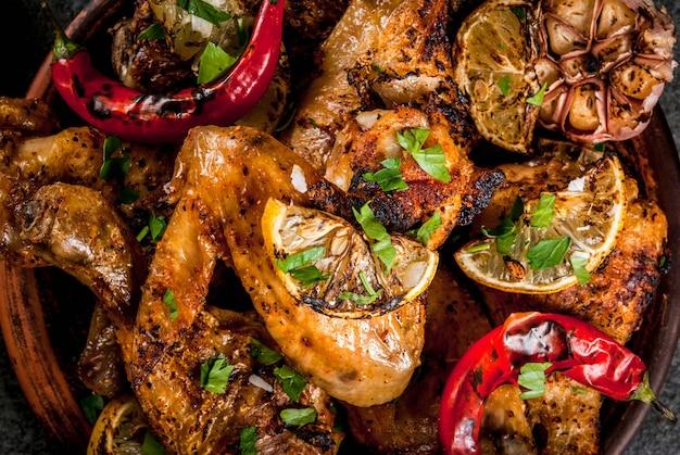 Letnie jedzenie. pomysły na grilla, przyjęcie z grilla. udka z kurczaka, skrzydełka z grilla, smażone w ogniu. z ostrą papryczką chili, cytryną i sosem bbq. ciemny kamienny stół, na czarnej płycie zamknij widok z góry