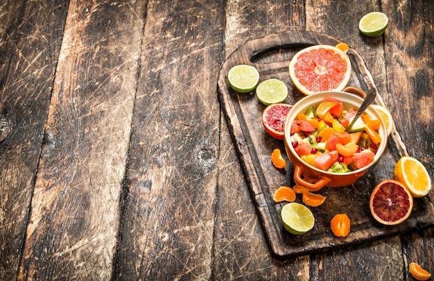 Letnie jedzenie. sałatka owocowa w misce. na drewnianym tle.