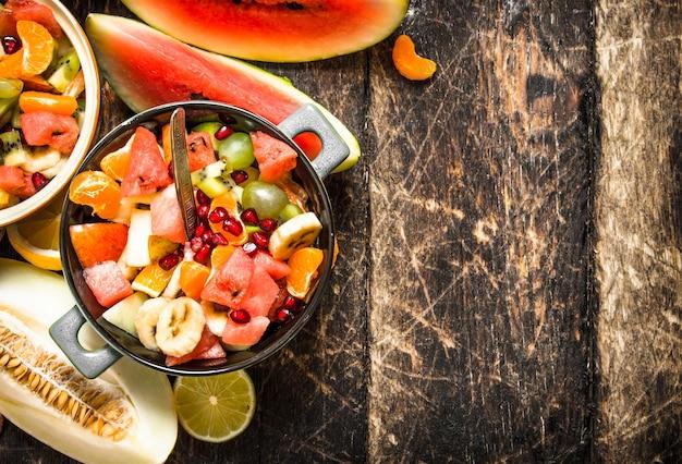 Letnie jedzenie. sałatka z owoców tropikalnych. na drewnianym tle.