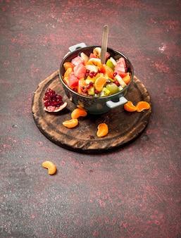 Letnie jedzenie tropikalna sałatka z owoców egzotycznych na tle rustykalnym