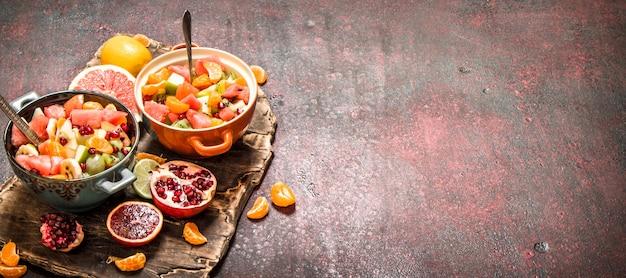 Letnie jedzenie. tropikalna sałatka z owoców egzotycznych. na tle rustykalnym.