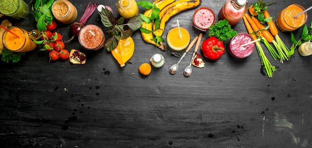 Letnie koktajle z warzyw, jagód i owoców. na czarnym tle.
