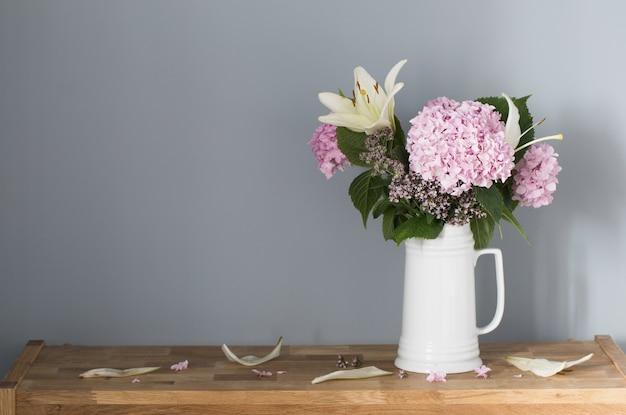 Letnie kwiaty w białym dzbanku na drewnianej półce