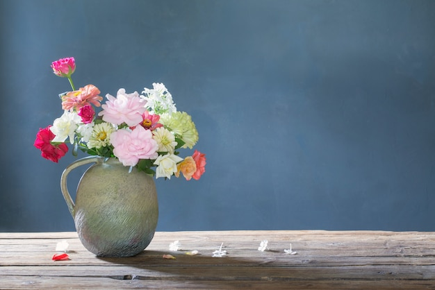 Letnie kwiaty w ceramicznym dzbanku na drewnianym stole na niebieskim tle