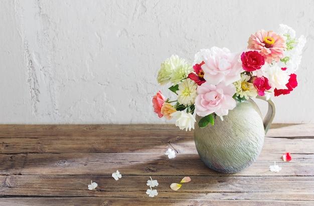 Letnie kwiaty w ceramicznym dzbanku na drewnianym stole na tle starej białej ściany