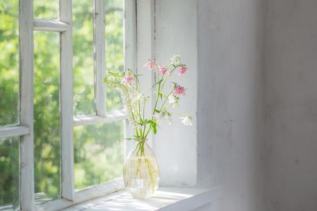 Letnie kwiaty w wazonie na parapecie w słońcu