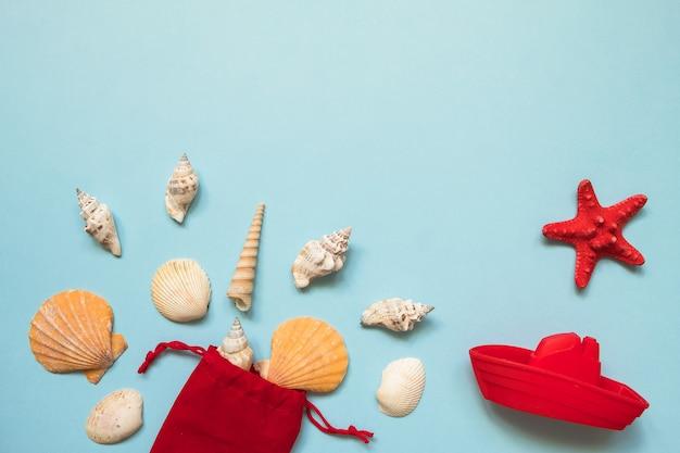 Letnie mieszkanie leżał z muszelek, czerwona rozgwiazda i zabawka łodzi na niebieskim morzu