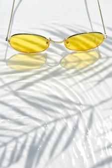 Letnie mieszkanie leżało z żółtymi okularami przeciwsłonecznymi na tle wody z cieniami liści palmowych i przestrzeni kopii. koncepcja gorącego letniego dnia na plaży.