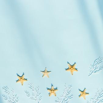Letnie mieszkanie morskie leżało z gwiazdami morza i białym koralem na niebieskim tle koncepcja odpoczynku w czasie letnim