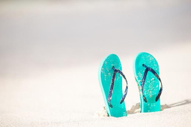 Letnie miętowe klapki z okularami przeciwsłonecznymi na białej plaży