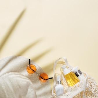 Letnie minimalne tło z kapeluszem przeciwsłonecznym, kolorowymi okularami przeciwsłonecznymi i produktem kosmetycznym