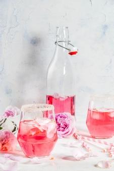 Letnie napoje orzeźwiające. jasnoróżowy koktajl różany z winem różanym, herbacianymi płatkami róż, cytryną. na białym kamiennym betonowym stole. z różowymi rurkami w paski, płatkami i kwiatami róży. skopiuj miejsce