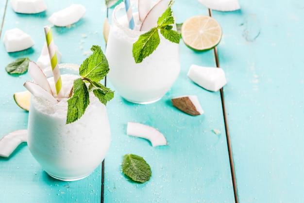 Letnie napoje orzeźwiające, koktajle. mrożone kokosowe mojito z limonką i miętą. pina colada. na jasnoniebieskim zielonym drewnianym stole ze składnikami. skopiuj miejsce