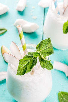 Letnie napoje orzeźwiające, koktajle. mrożone kokosowe mojito z limonką i miętą. pina colada. na jasnoniebieskim zielonym drewnianym stole ze składnikami. skopiuj widok zamknij przestrzeń