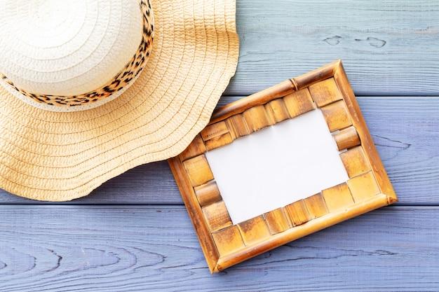 Letnie okulary przeciwsłoneczne w tle, słomkowy kapelusz na niebieskim drewnianym tle