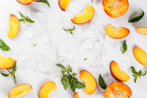 Letnie orzeźwiające koktajle, napoje. składniki na schłodzoną brzoskwiniową herbatę miętową, lód i kawałki świeżej żółtej brzoskwini. widok z góry