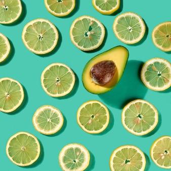 Letnie owoce cytrusowe plasterki cytryny wzór z połową awokado z cieniami na jasnozielonym tle. pojęcie zdrowej diety. widok z góry.