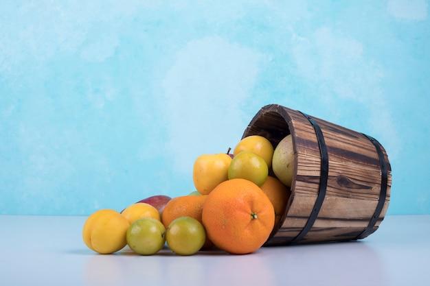 Letnie owoce mieszają się z drewnianego wiadra na niebiesko.