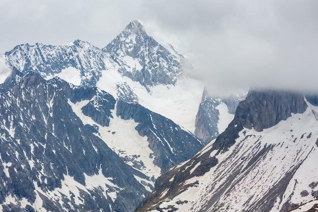 Letnie pochmurne alpy i widok na grzbiet bettmerhorn z lodowca great aletsch i opadu lodu (bettmeralp, szwajcaria)