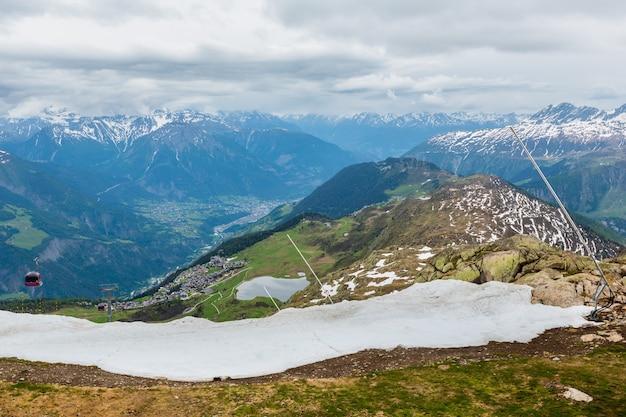 Letnie pochmurne górskie doliny alp i widok wioski bettmeralp z lodowca great aletsch i opadu lodu (bettmerhorn, szwajcaria)