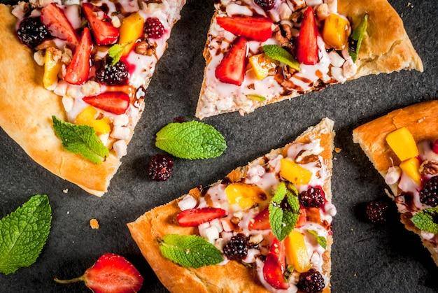 Letnie przekąski. jedzenie na imprezę. pizza owocowa ze śmietaną, porzeczkami, jogurtem, truskawkami, mango, brzoskwiniami, bananami, jeżynami, czekoladą, orzechami włoskimi, miętą. na czarnym stole. widok z góry lato