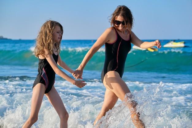 Letnie rodzinne wakacje na morzu, szczęśliwa matka i córka dziecko w strojach kąpielowych spacerujące wzdłuż brzegu morza, trzymając się za ręce, ciesząc się wodą i wieczornym słońcem zachodzącego słońca