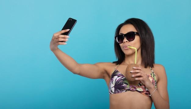 Letnie selfie. czarna dziewczyna w stroju kąpielowym fotografuje się ze świeżym koktajlem na telefon.