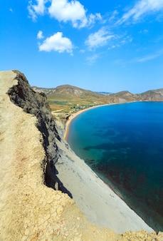 Letnie skaliste wybrzeże i kemping na piaszczystej plaży (tihaja bay, krym, ukraina). wszystkie narody i samochody są nie do poznania.