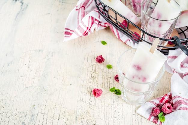 Letnie słodkie desery, domowe popsicles lodów ekologicznych z malin i jogurtu