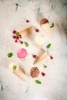 Letnie słodkie jagody i desery, różne smaki lodów w rożkach różowy (malinowy), waniliowy i czekoladowy z miętą na lekkim betonie