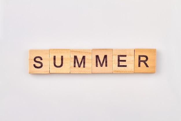 Letnie słowo napisane w drewnianych kostkach. pojęcie sezonu na białym tle.