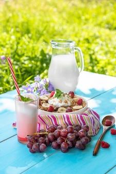 Letnie śniadanie na świeżym powietrzu z owsianką, malinami i winogronami oraz pysznym jogurtem
