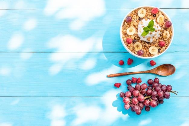 Letnie śniadanie na świeżym powietrzu z owsianką z malinami, bananem i winogronami. skopiuj miejsce. widok z góry.