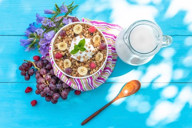 Letnie śniadanie na świeżym powietrzu z owsianką z malinami i winogronami oraz pysznym jogurtem ze słomką na niebieskim drewnianym stole.