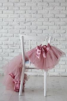 Letnie sukienki dziecięce zawieszają się na wieszakach na krześle dziecięcym z tyłu. miejsce na tekst