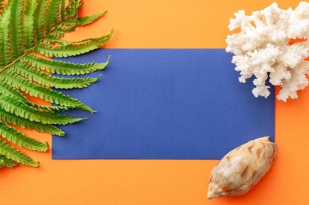 Letnie tło niebieska koperta, liść paproci, muszla, koral na pomarańczowym tle