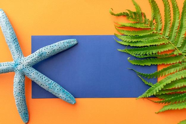 Letnie tło niebieska koperta, rozgwiazda, liść paproci, na pomarańczowym tle