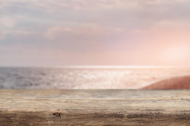 Letnie tło z drewnianą podstawą i widokiem na morze o zachodzie słońca