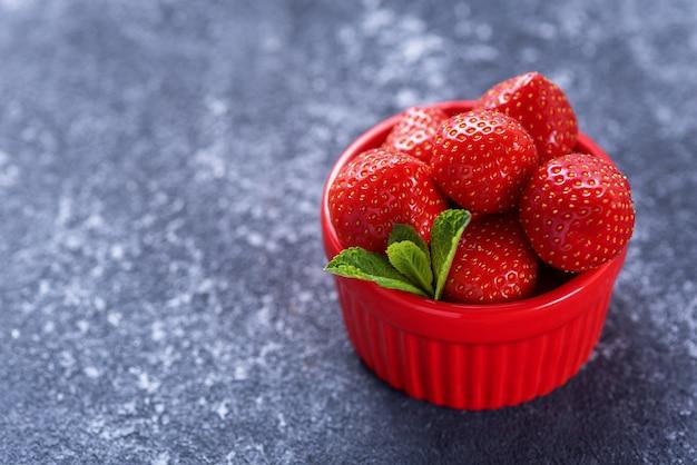 Letnie truskawki w czerwonej misce z miętą na szaro