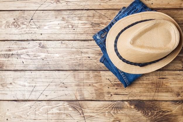 Letnie ubrania damskie. płaskie zdjęcie mody świeckich. niebiescy dżinsy i słońce kapelusz na drewnianym tle. skopiuj miejsce
