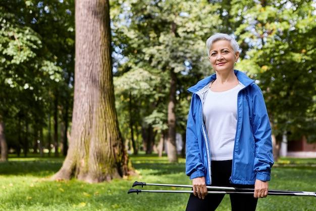 Letnie ujęcie pięknej, stylowej starszej osoby trenującej na świeżym powietrzu z kijkami narciarskimi obiema rękami podczas skandynawskiego spaceru. energia, aktywność, dobre samopoczucie, ludzie w podeszłym wieku i koncepcja sportu