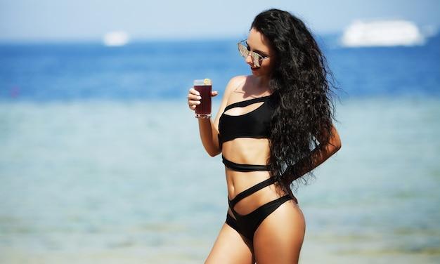 Letnie wakacje. atrakcyjna młoda dziewczyna z długimi włosami siedzi blisko morza, ubrana w białą sukienkę i okulary przeciwsłoneczne.